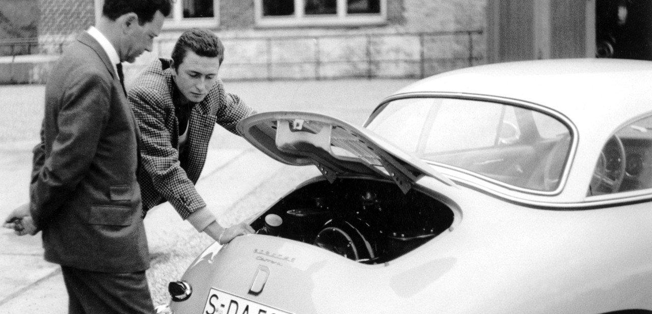 Dos personas revisando el motor trasero de un Porsche 356