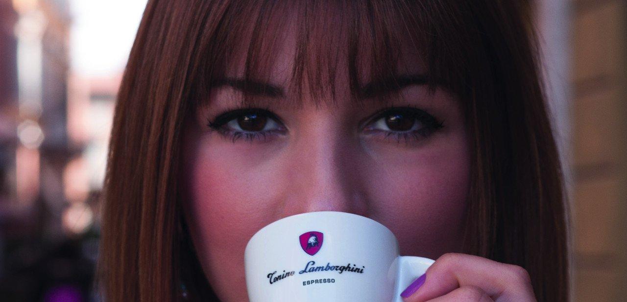 Modelo bebiendo un café en una taza Lamborghini