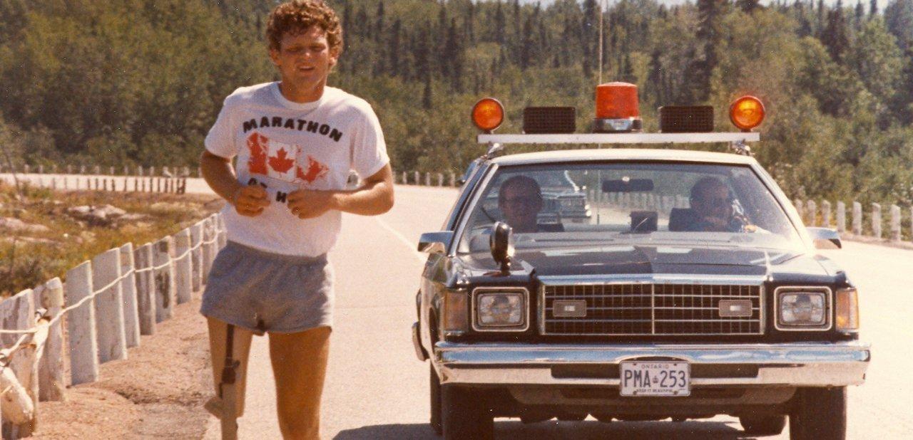 Terry Fox corriendo con un vehículo policial detrás