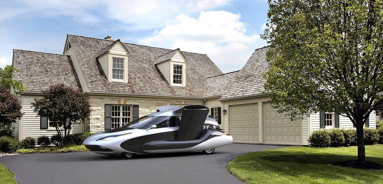 Un coche volador Terrafugia TF-X aparcado frente a una casa