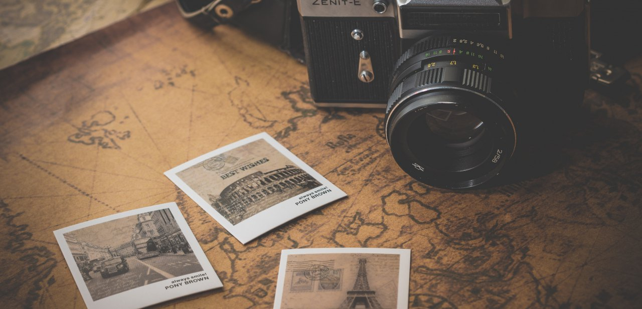 Una cámara fotográfica junto a instantáneas de varios destinos