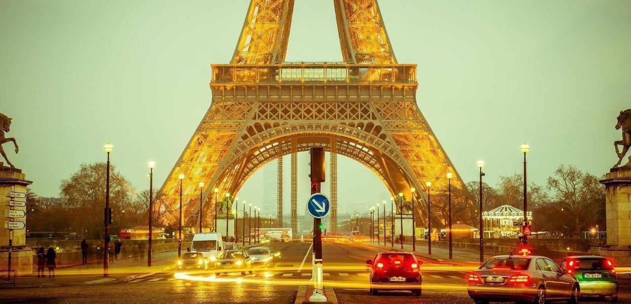 Una transitada calle parisina con la Torre Eiffel al fondo