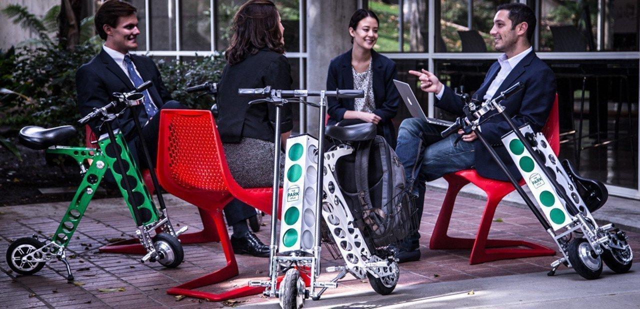 Varios scooters Urb-E plegados en una terraza de bar