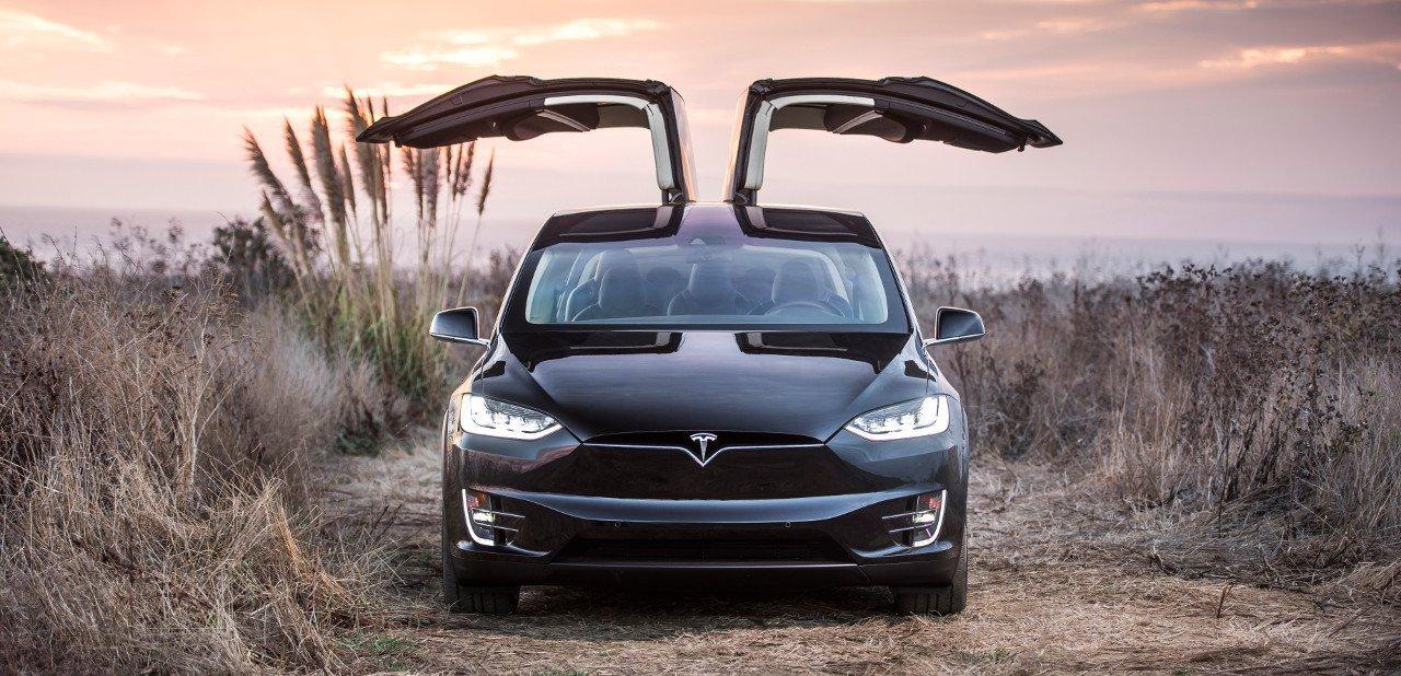 Vista frontal de un Tesla X con las puertas traseras abiertas
