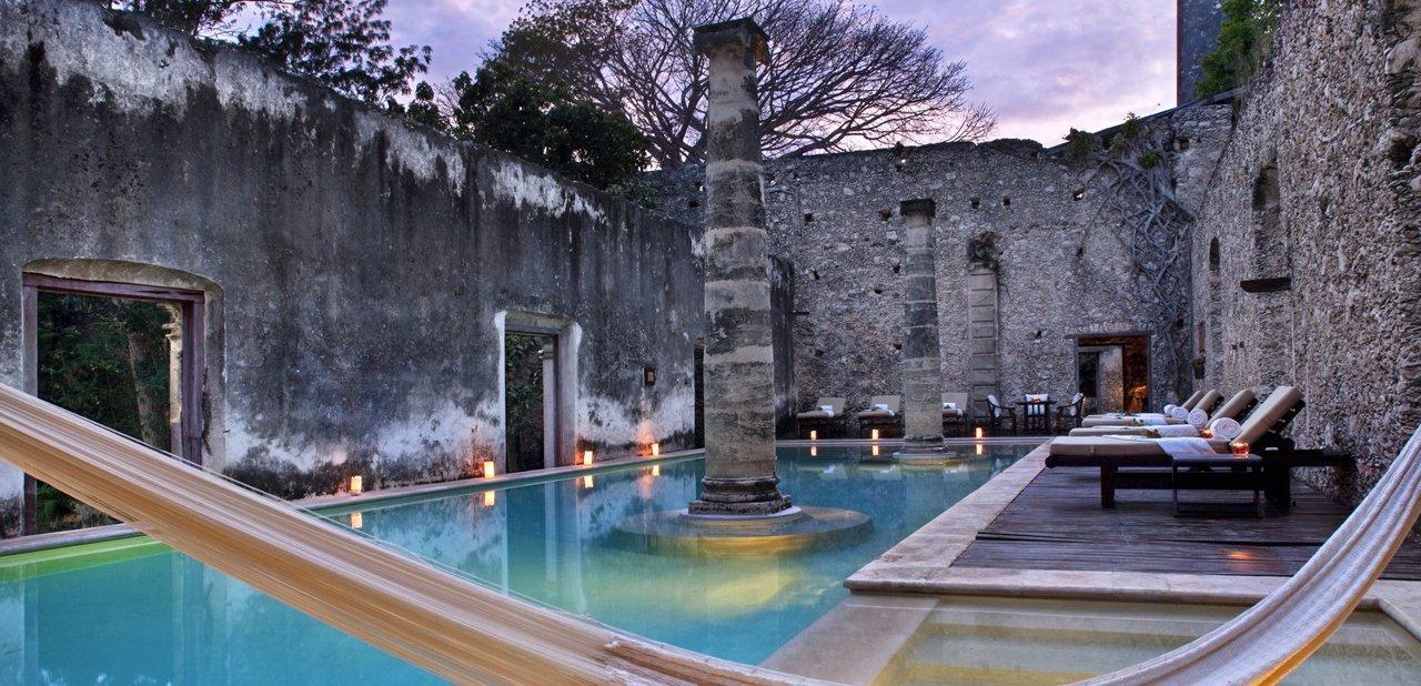 Vista nocturna de la piscina de la Hacienda Uayamon